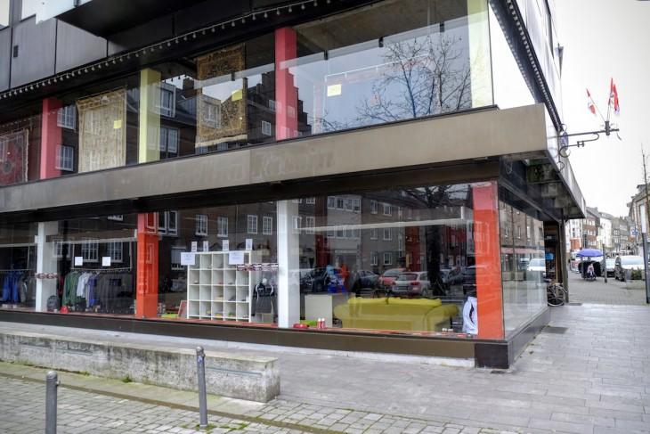 """Eingangs der Straße empfängt den Besucher ein modernistischer Bau, der früher das alteingesessene Fachgeschäft """"Porzellan Fassin"""" beherbergte. Die Reste des Schriftzugs sind noch gut zu lesen. Mittlerweile ist darin…"""