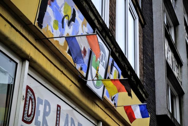 Wie unbarmherzig der Wind durch die Steinstraße pfeift, zeigen die Überreste dieser niederländischen Flagge an einer Fassade