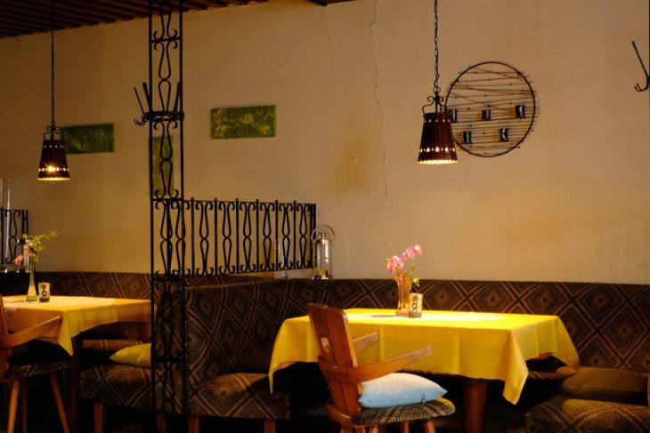Schmiedeeiserne Raumteiler, frische Blumen: Innenansichten einer traditionsreichen Gaststätte