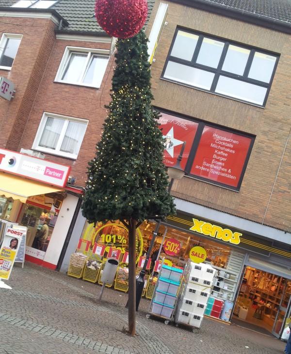 Kerzengerade ragt der Weihnachtsbaum vor Xenos in die Höhe, der Rest der Welt aber… oje! (Foto © Rudolf Stein)