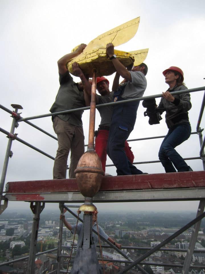 Nach Schönheitskur endlich wieder da, wo er hingehört: 3 kräftige Männer hieven das Klever Wappentier auf die Spitze des Schwanenturms (Foto © Kleve Marketing)