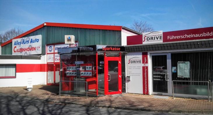 Dominantes Rot, wie die sprichwörtlichen Zahlen: der Neubau der Sparkassen-Hauptstelle inmitten von Caldenhoven (Autoteile) und S-Drive (Autolizenzen)