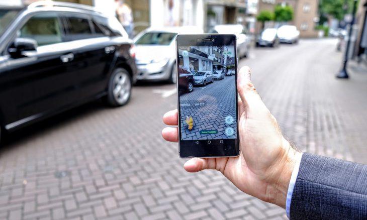Für die meisten Menschen eine normale Straße in der Innenstadt, doch das Handy-Display beweist: mitten auf der Fahrbahn treibt sich ein niederes Pokémon herum